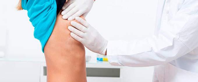 Маммолог осматривает кожу груди